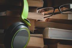 Fones de ouvido e monóculos que sentam-se em pilhas de livros imagem de stock royalty free