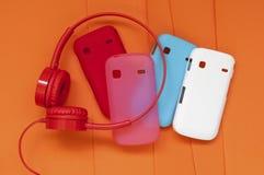 Fones de ouvido e tampas brilhantes para o telefone em um backgrou alaranjado Fotografia de Stock