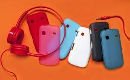 Fones de ouvido e tampas brilhantes para o telefone em um backgrou alaranjado Fotos de Stock