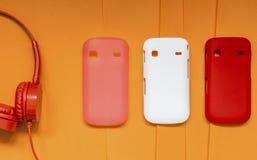 Fones de ouvido e tampas brilhantes para o telefone em um backgrou amarelo Fotos de Stock Royalty Free