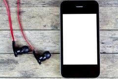Fones de ouvido e telefone esperto em um de madeira Fotos de Stock