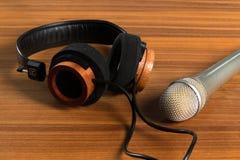 Fones de ouvido elegantes e um microfone do estúdio em uma tabela de madeira fotos de stock royalty free