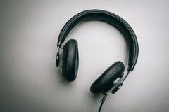 Fones de ouvido em um fundo cinzento Imagens de Stock