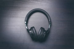 Fones de ouvido em um fundo escuro Acessórios da música Fones de ouvido de Bluetooth sem cabo imagem de stock