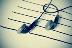 Fones de ouvido em um pessoal que simula notas musicais Imagens de Stock