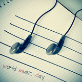Fones de ouvido em um pessoal que simula notas musicais e o mundo do texto Imagens de Stock