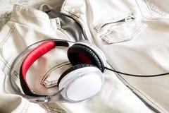 Fones de ouvido em um revestimento branco Imagens de Stock