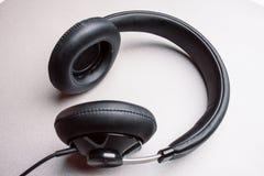 Fones de ouvido em uma luz - mesa cinzenta Foto de Stock