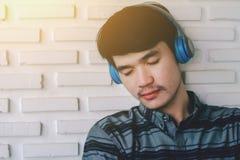 Fones de ouvido de escuta da música do homem gay novo do moderno Fotos de Stock