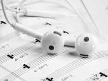 Fones de ouvido mucic profissionais na folha de música Imagem de Stock Royalty Free