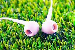Fones de ouvido na grama Fotografia de Stock Royalty Free
