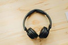Fones de ouvido na textura de madeira da mesa na luz do dia fotos de stock