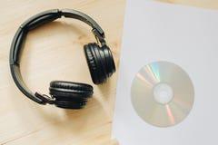 Fones de ouvido na textura de madeira da mesa na luz do dia e no CD no Livro Branco fotos de stock