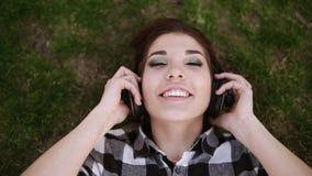 Fones de ouvido nas mãos fêmeas Menina encantador que encontra-se nela para trás na grama, pondo sobre fones de ouvido e escutand vídeos de arquivo
