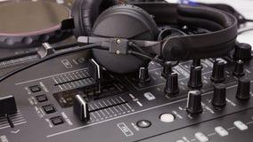 Fones de ouvido no console e no misturador da mistura do DJ Fotografia de Stock