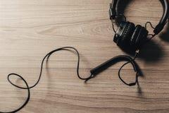Fones de ouvido no fundo de madeira escuro imagens de stock