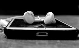 Fones de ouvido no telefone fotografia de stock