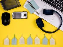 Fones de ouvido, portátil, rato, câmera, carteira, pena, notas e planos de papel, vista lisa fotografia de stock
