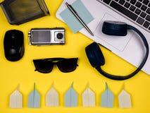Fones de ouvido, portátil, rato, câmera, carteira, pena, notas, máscaras e planos de papel, vista lisa imagens de stock