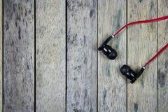 Fones de ouvido postos sobre a prancha de madeira Imagens de Stock