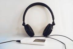 Fones de ouvido pretos com o jogador no close-up branco do fundo imagens de stock
