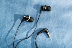 Fones de ouvido pretos com sombra no fundo de calças de ganga fotografia de stock