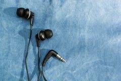 Fones de ouvido pretos com sombra no fundo de calças de ganga, espaço para o texto fotos de stock royalty free