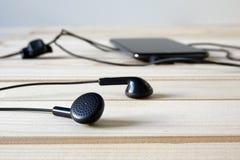 Fones de ouvido pretos conectados ao telefone celular na tabela de madeira fotos de stock