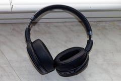 Fones de ouvido pretos no fundo de mármore 2 imagens de stock