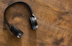 Fones de ouvido pretos no fundo de madeira da tabela com espaço da cópia Vista superior fotos de stock