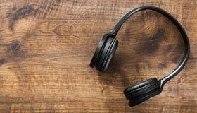 Fones de ouvido pretos no fundo de madeira da tabela com espaço da cópia Vista superior foto de stock royalty free