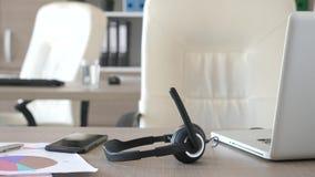 Fones de ouvido que encontram-se na mesa no escritório do apoio do cuidado do cliente vídeos de arquivo