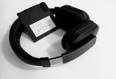 Fones de ouvido sem fio e uma disquete retro com arquivos da música fotografia de stock royalty free