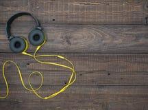 Fones de ouvido de um grande tamanho com um fio amarelo em uma tabela de madeira imagem de stock royalty free
