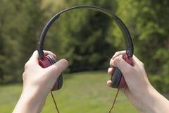 fones de ouvido Vermelho-pretos nas mãos na perspectiva das árvores coníferas fotos de stock royalty free
