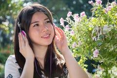 Fones de ouvido vestindo da jovem mulher bonita asiática no jardim fotos de stock royalty free