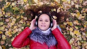 Fones de ouvido vestindo da jovem mulher feliz bonita que encontram-se nas folhas de outono que escutam a música Estação, tecnolo video estoque