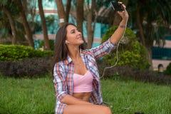 Fones de ouvido vestindo da jovem mulher feliz e tomada de uma foto no parque que senta-se no freio Selfie fêmea atrativo foto de stock royalty free