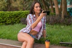 Fones de ouvido vestindo da jovem mulher feliz e tomada de uma foto no parque que senta-se no freio Selfie fêmea atrativo fotos de stock