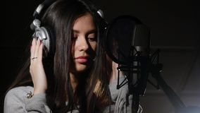 Fones de ouvido vestindo da jovem mulher no estúdio de gravação perto do microfone Fotos de Stock