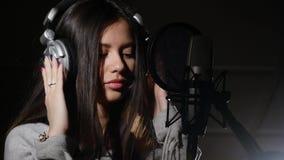 Fones de ouvido vestindo da jovem mulher no estúdio de gravação perto do microfone Imagem de Stock
