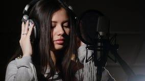 Fones de ouvido vestindo da jovem mulher no estúdio de gravação perto do microfone Imagens de Stock Royalty Free