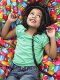 Fones de ouvido vestindo da menina que reclinam no Beanbag fotografia de stock