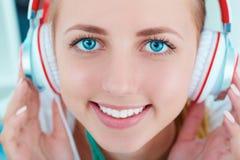 Fones de ouvido vestindo de sorriso caucasianos bonitos da mulher e música de escuta Fotografia de Stock Royalty Free