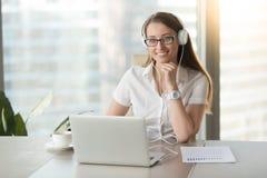 Fones de ouvido vestindo de sorriso da mulher de negócios com o portátil que levanta em w fotos de stock royalty free