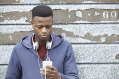 Fones de ouvido vestindo do adolescente e escuta a música em S urbano imagens de stock