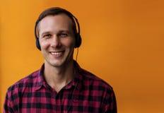 Fones de ouvido vestindo do homem considerável feliz novo e para apreciar a música sobre o fundo amarelo imagens de stock royalty free