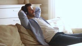Fones de ouvido vestindo do homem da calma que refrigeram a escuta a música em casa video estoque