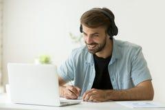 Fones de ouvido vestindo de sorriso do homem que olham a fatura do tela de computador Fotos de Stock Royalty Free