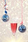 Fonkelende champagne en twee hangende snuisterijen tegen Kerstmisli stock fotografie